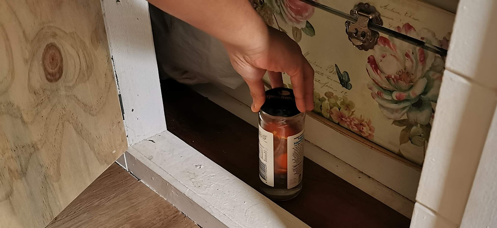 A man places the reused jar full of white vinegar and mandarin peel in a dark cupboard.
