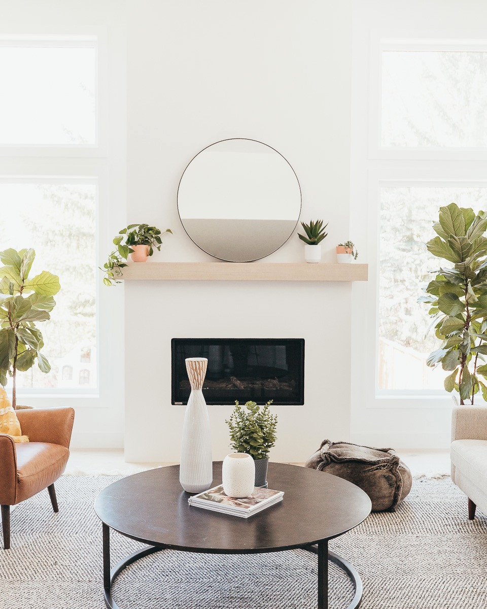 A bright and airy living room with a white fireplace and oak mantel.
