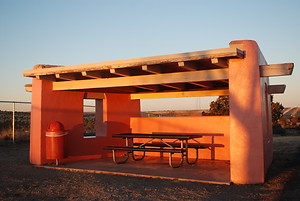 A picnic table and garbage can in a roofed enclosure made with three walls of colorful pink adobe and a wooden roof.