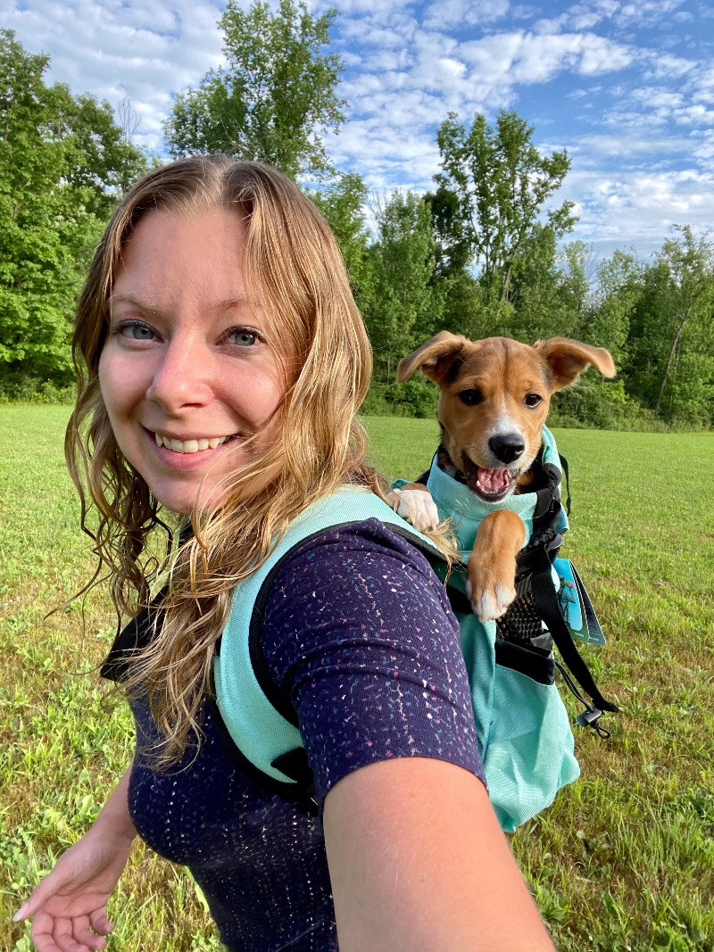 A woman walking with her dog in a doggy backpack.