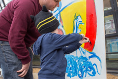 A father and son painting a dragon shield at Dan Donovan's art station