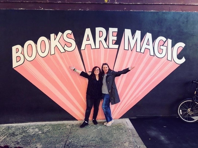Two women stand in front of a sign that says Books Are Magic. They are smiling.