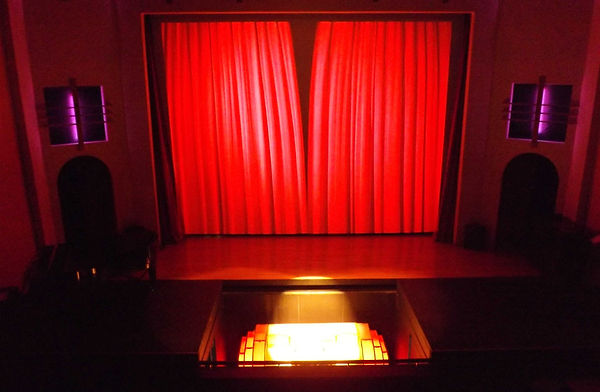 Curtains about to open on stage behind a Wurlitzer Organ lit up, lowered in a pit.
