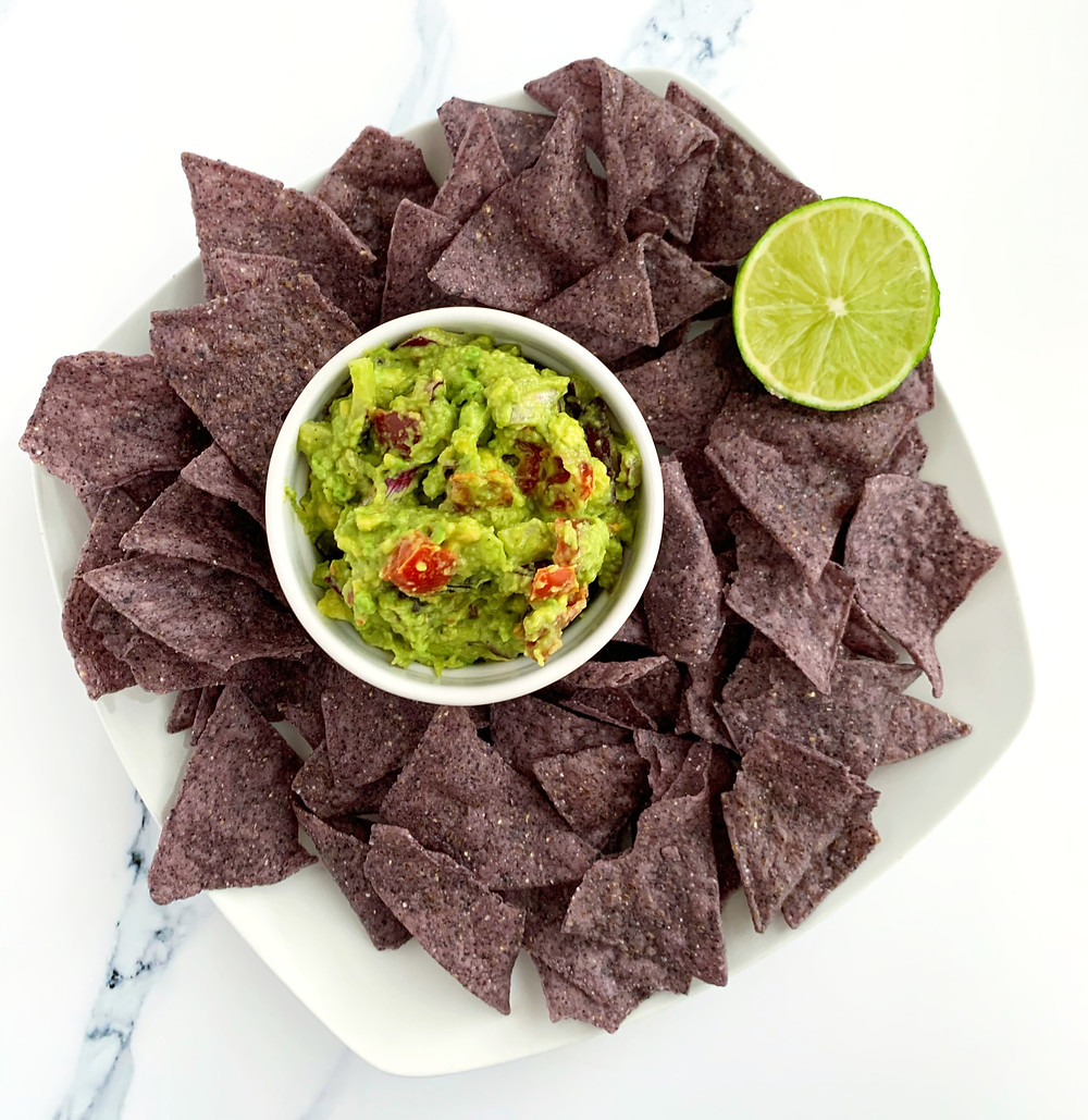 overhead shot of creamy 5-minute guacamole with blue tortilla chips and a slice of lime