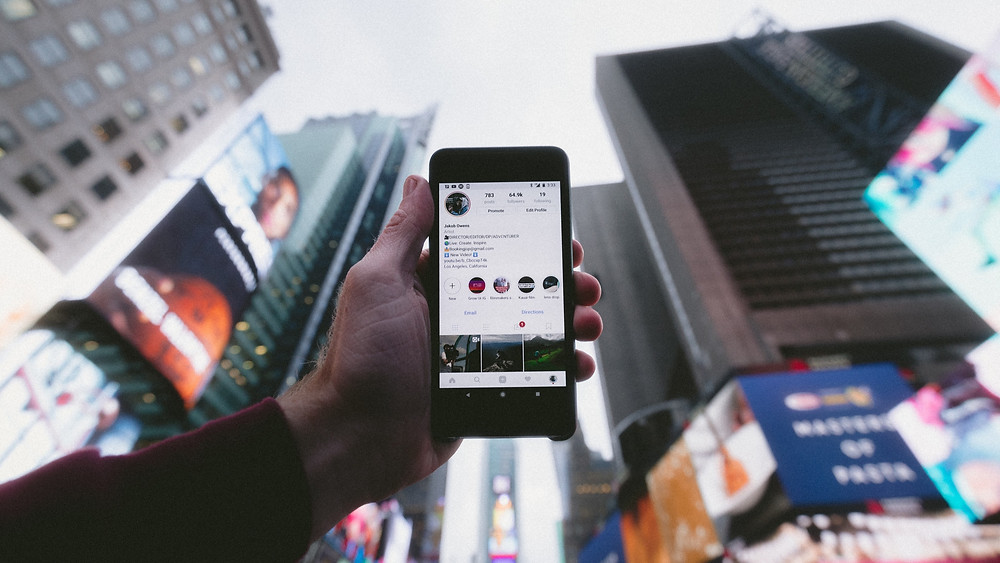 Man holding up iPhone with an Instagram profile on the screen, while standing in Times Square, New York