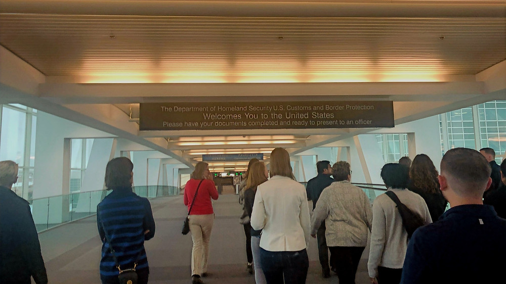 "A group of people walking towards a sign that reads ""the Department of Homeland Security U.S. Customs and Border Protection welcomes you to the United States! Please have your documents complete and ready to present to an officer""."