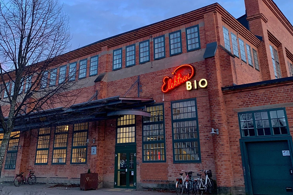 En gammal tegelbyggnad i industristil med Elektras röda neonskylt på fasaden.