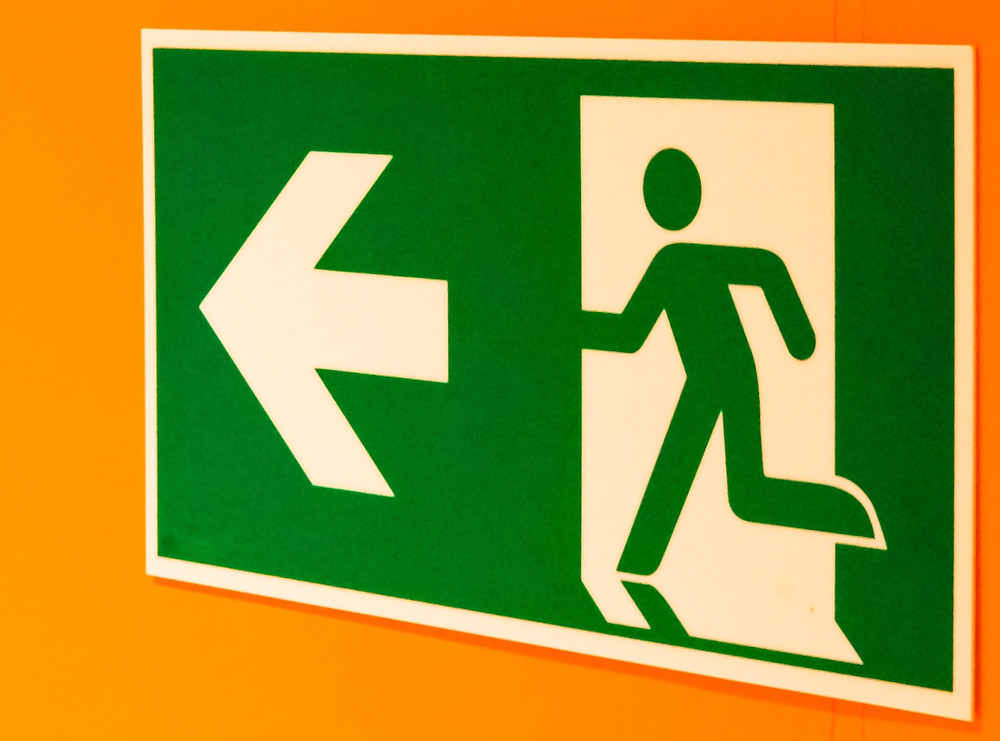 A Green Fire Exit Sign with an arrow in white pointing to the left with a person walking though an open door