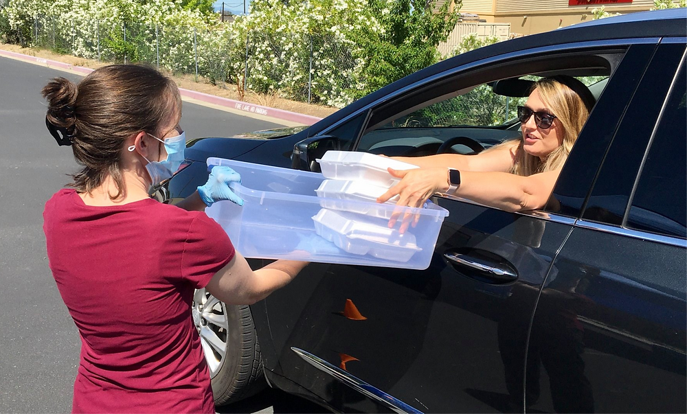 """Staff from the Tehama County distribute """"grab-and-go"""" meals during COVID-19, as part of a partnership with First 5 Tehama County and the Red Bluff Union Elementary School District."""