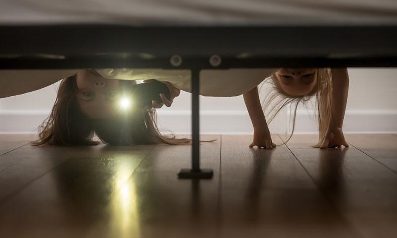 Две исплашени девојчиња проверуваат дали има сокриено чудовиште под нивниот кревет