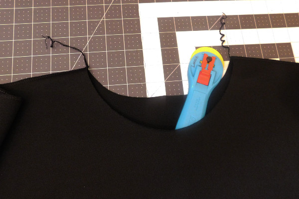 Image shows the neck opening with completed shoulder seams. Fabric is black, so to help show the depth of the new neck opening, there is a blue rotary cutter named Lonnie tucked in between the front and back to help show the neckline due to the difficulty in photographing black on black.