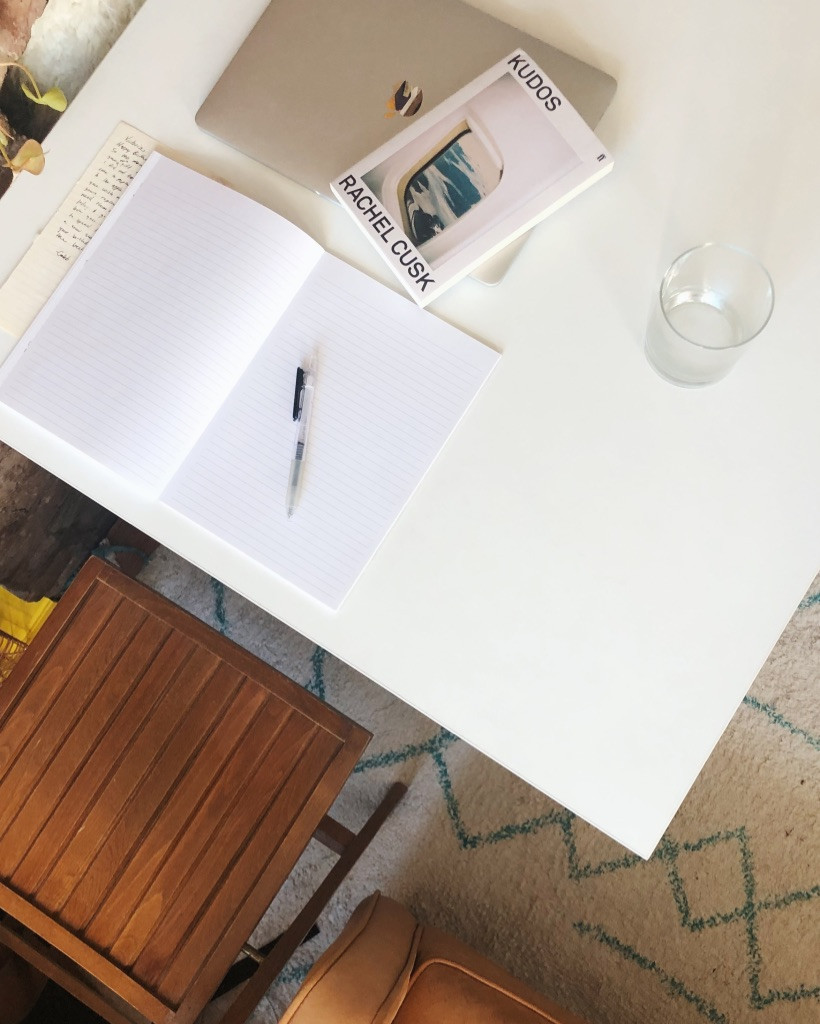 A blank journal, open on a desk with a computer and a book next to it.