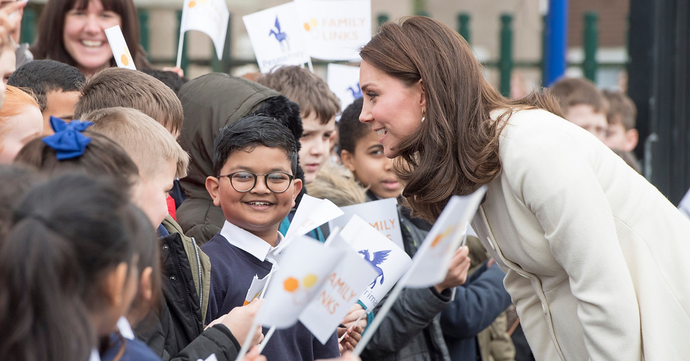 The Duchess of Cambridge is talking to a group of school children. The children are holding flags.
