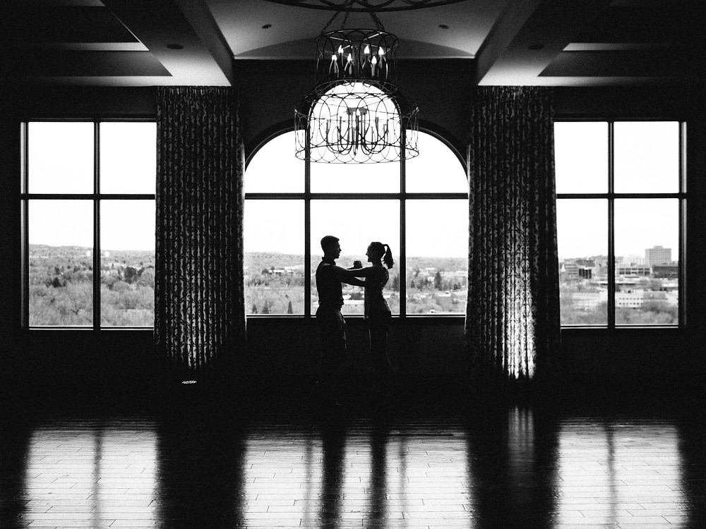 Couple dancing in front of windows, backlit