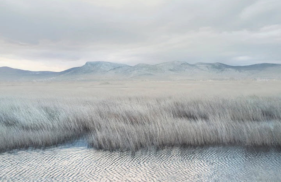 minimalist white landscape of a river passing next to a field below the mountains