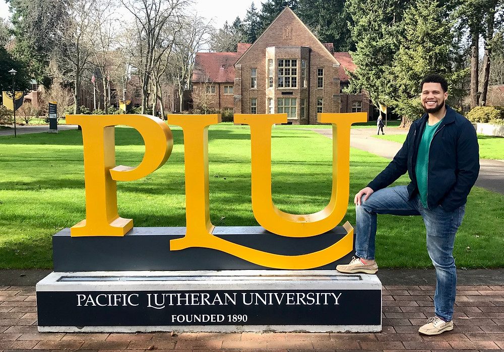 Akeem Bentick poses with the Pacific Lutheran University sign on his campus.