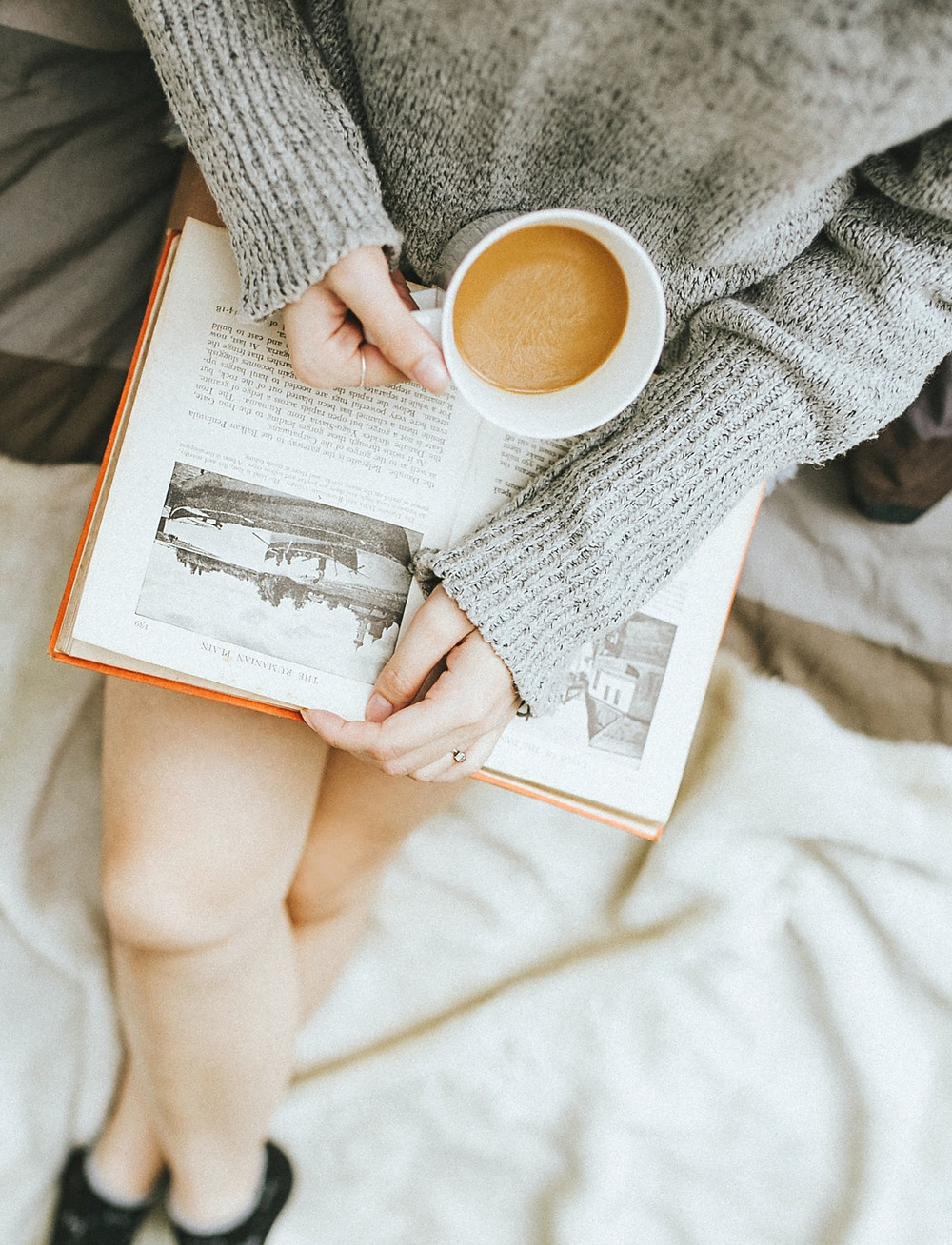 Woman sitting on couch with tea and a book