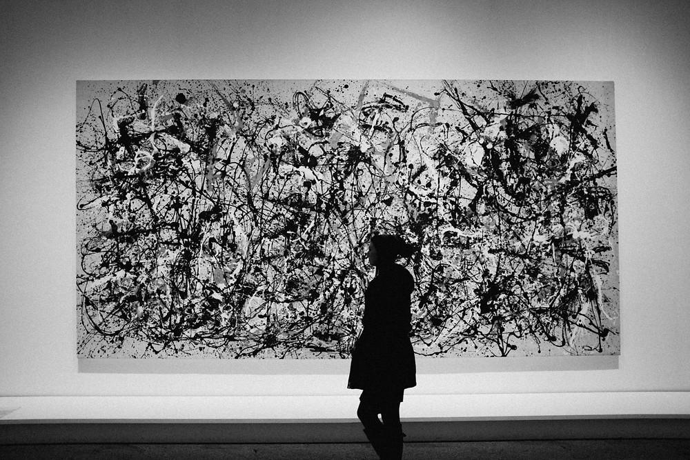 A girl framed in front of a Jackson Pollock painting at the Met.