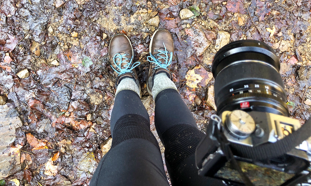 Waterproof hiking boots on fall leaves and mud