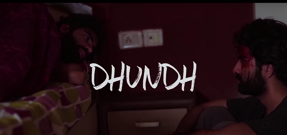 A title card reading 'Dhundh' which also shows two versions of the same man looking at one another. One is sitting, blood smeared across his face, the other lying on a bed afraid.
