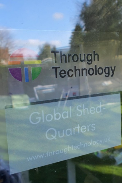 "A sign on a garden office saying ""Through Technology Global Shedquarters"""