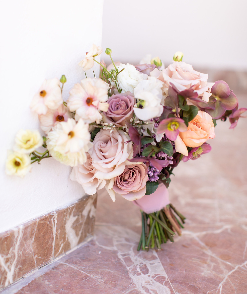 Beautiful lush floral heavy purple bridal bouquet filled with lilac, hellebores, roses and butterfly ranunculus made by San Diego wedding florist Le Champange Projects for a stunning Spring wedding at Rancho Las Lomas in Orange County, CA with a purple color palette.