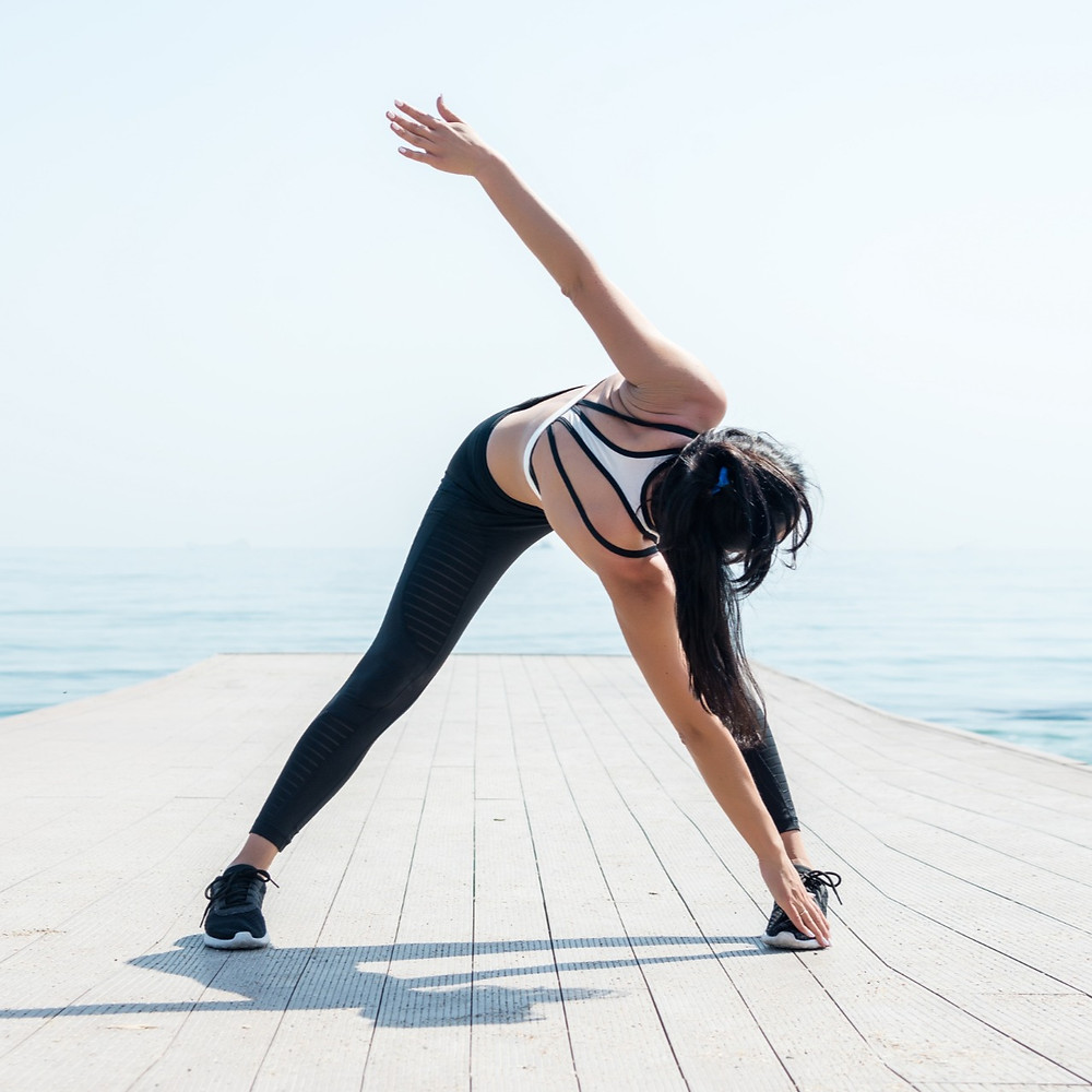 women stretching by doing a bent over side twit