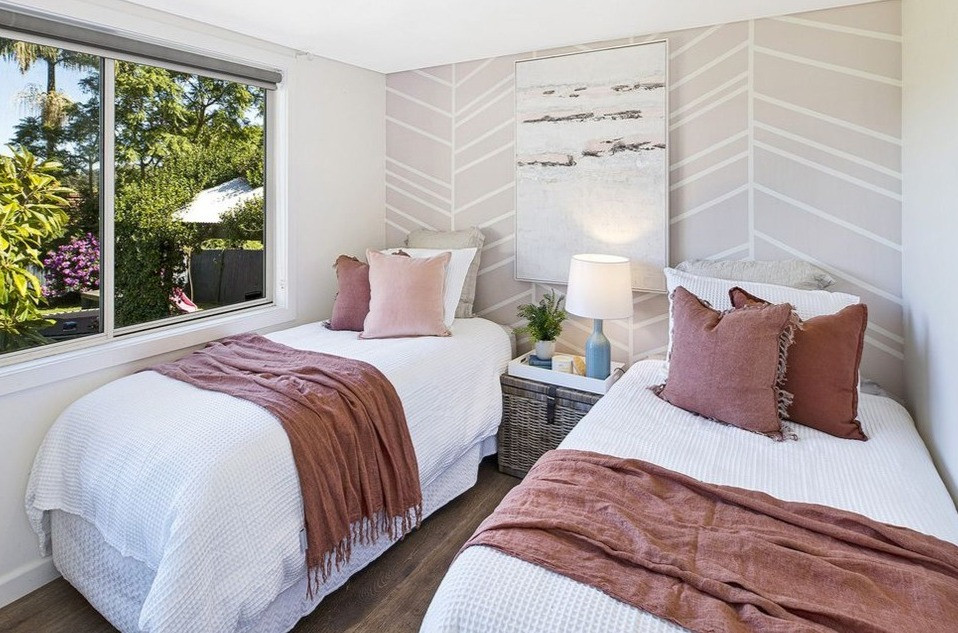 Childrens bedroom property staged with beautiful linens, atwork, side table and settings