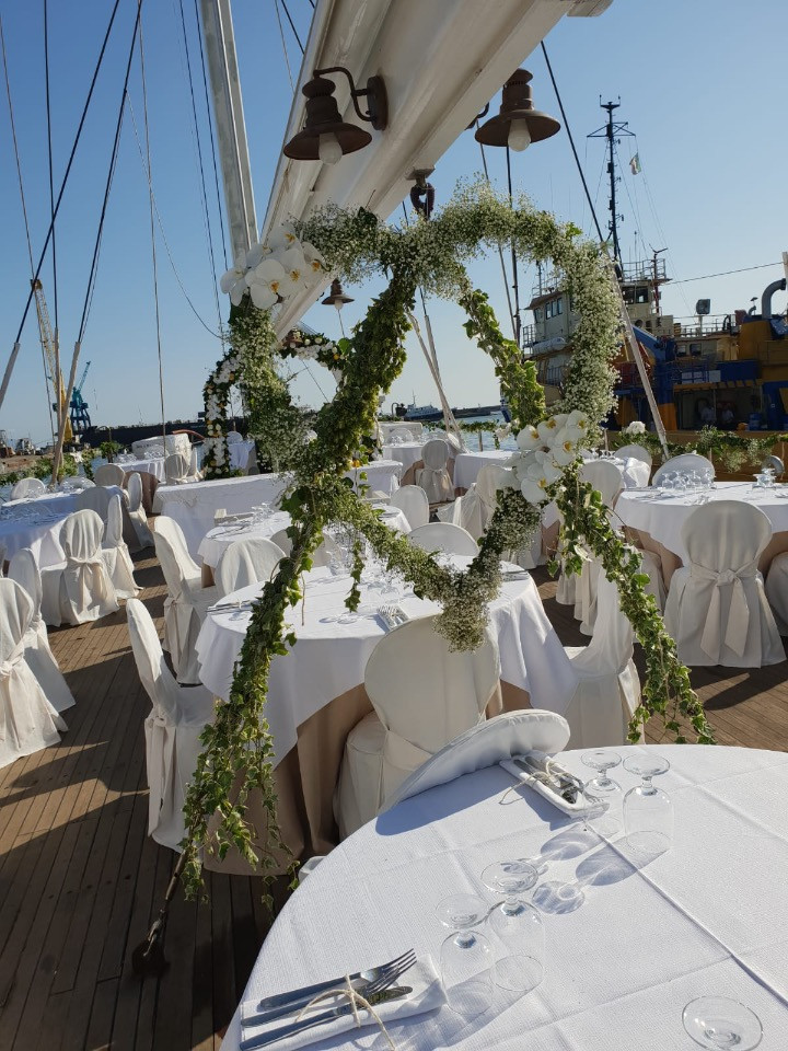For this wedding, the bride has chosen to serve the banquet on the deck of the sailing ship. The total white chosen as a palette is broken by a very pretty heart of Gypsophila placed between the tables in the center of the deck of the ship