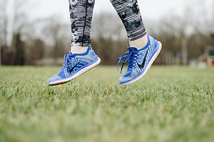A jogger is seen jumping in a close up view of her tennis shoes on a green expanse of lawn.