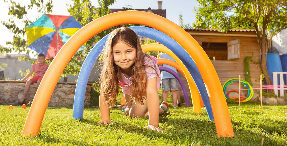 Little girl crawling through backyard toy playground.
