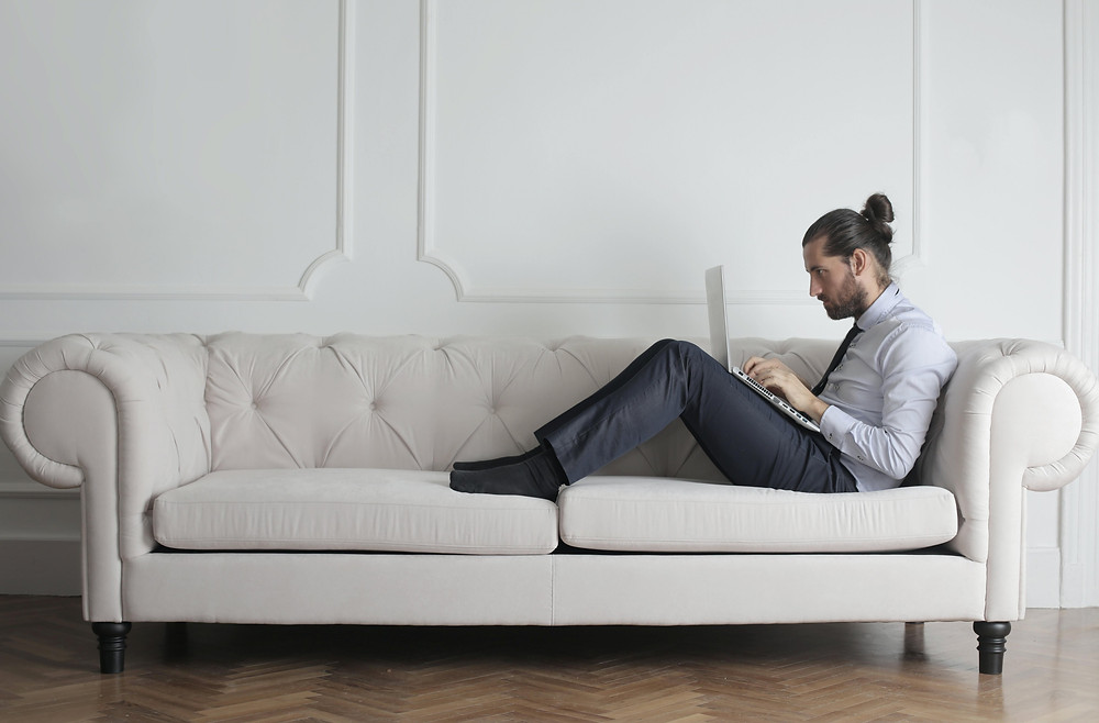 A man sitting on a white couch typing on a laptop