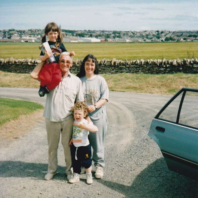 Grandad, on one of his trips to Orkney. Pictured here with my sister on his shoulder, myself with the grumpy face and my mum behind.