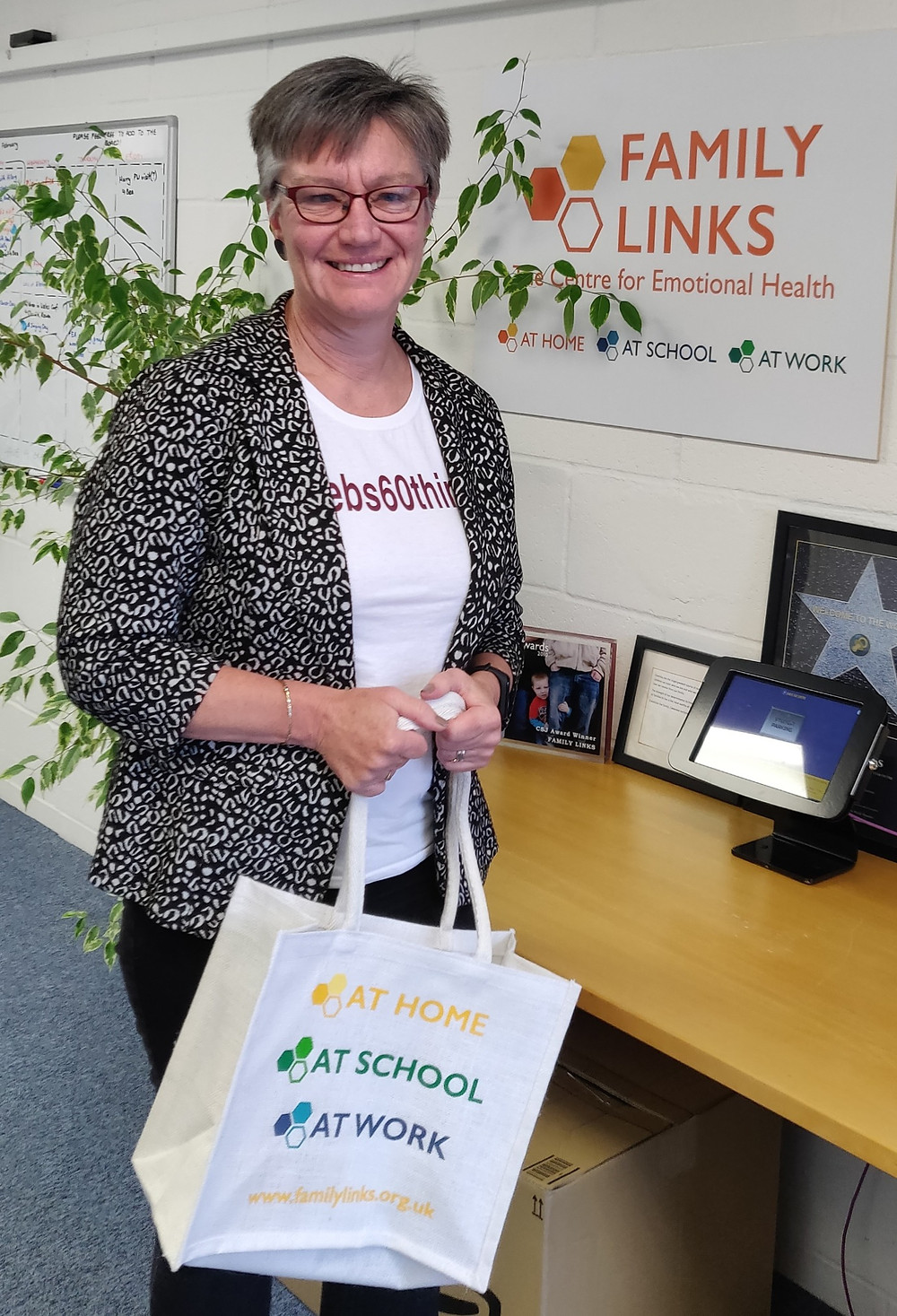 Deborah Wallis stands holding a Links tote bag, against a wall with the Family Links logo in the background