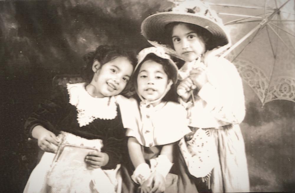 tres niñas disfrazadas con sombrero y sombrillas