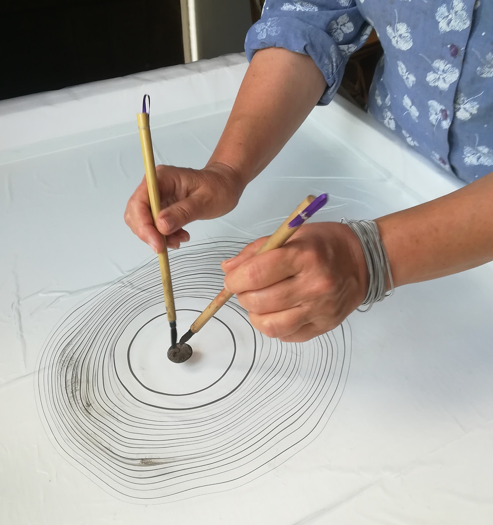 Placing circles of ink onto the water surface to create a piece of suminagashi