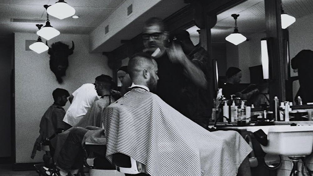 Black and white image of a barber shop with barber cutting mens hair