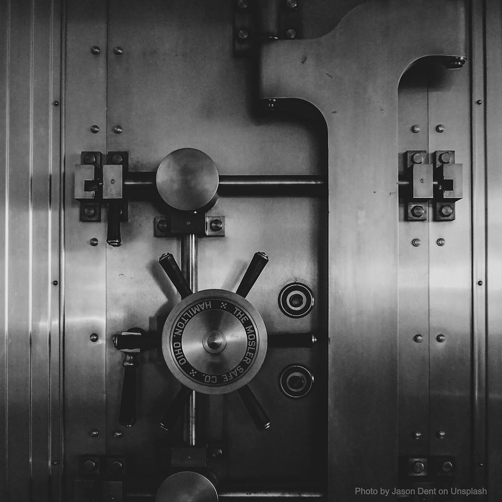 Antique steel bank vault door. Photo by Jason Dent on Unsplash