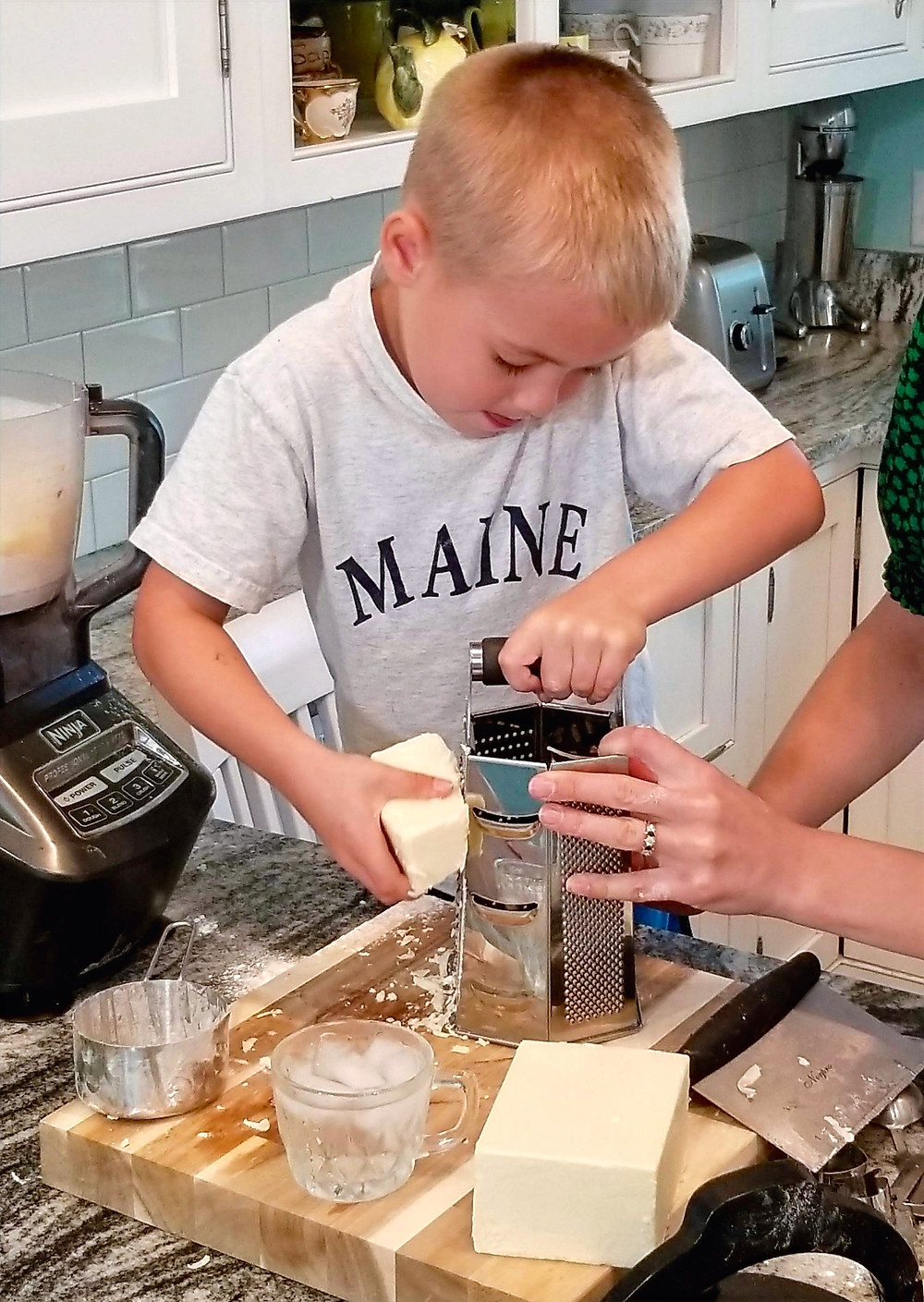 Young child (Thomas) grating cheese for goldfish crackers