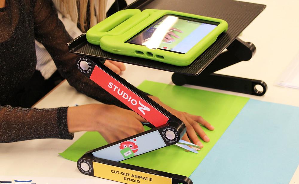Een foto van een close-up van een tablet op een houder. Een meisje plaats op een vel papier verschillende knipsels. Met de tablet worden foto's van deze composities gemaakt.
