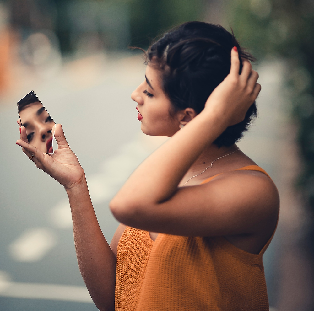 Girl standing in street looking at herself in a broken mirror.