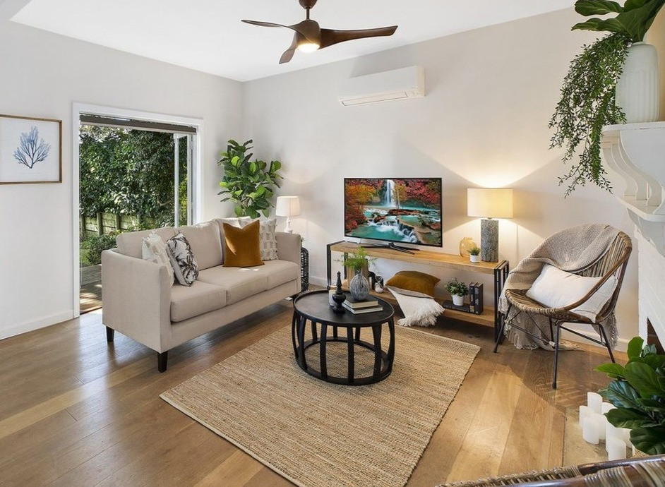 Property in Wamberal staged for sale with a bohemian feel using timber console, coffee table, jute rug and occassional chairs