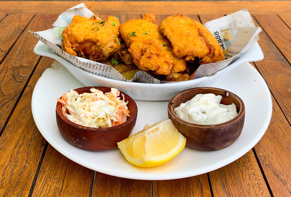 Serving of battered fish and chips with a side of coleslaw, tartar sauce, and a fresh lemon