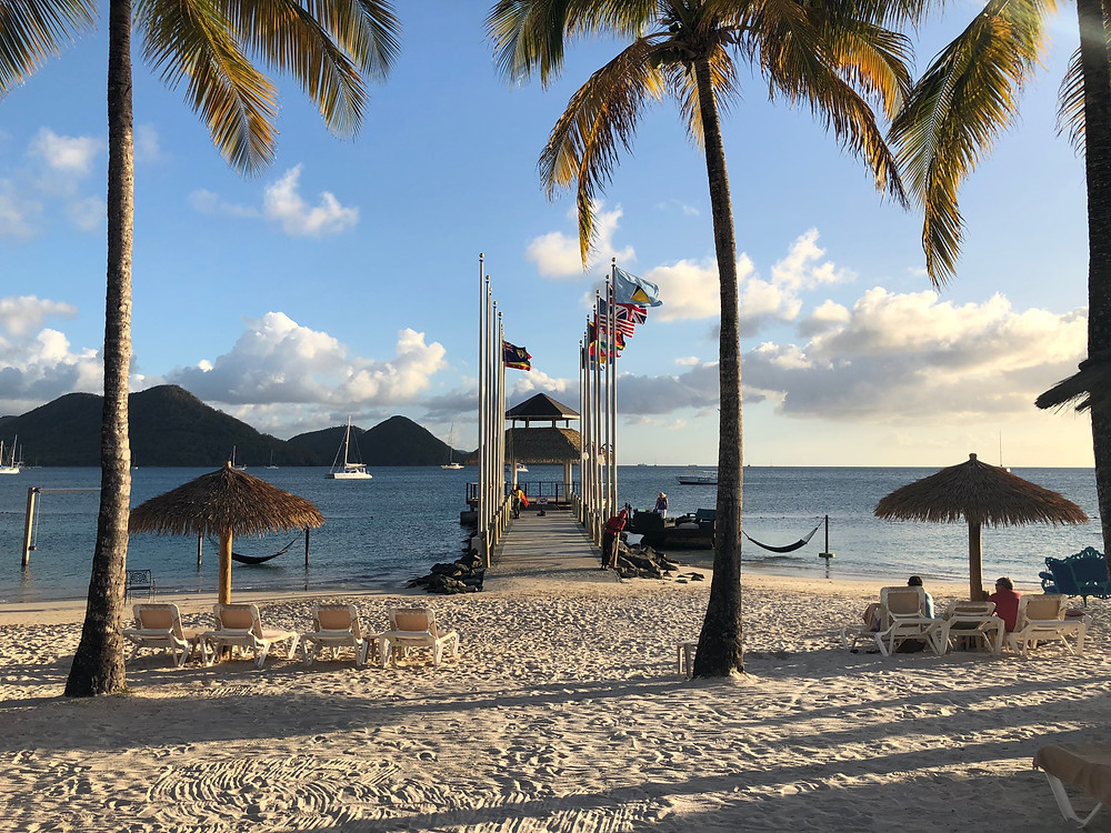 Flags and wooden pier holding a ceremony spot over the water for destination weddings in Saint Lucia
