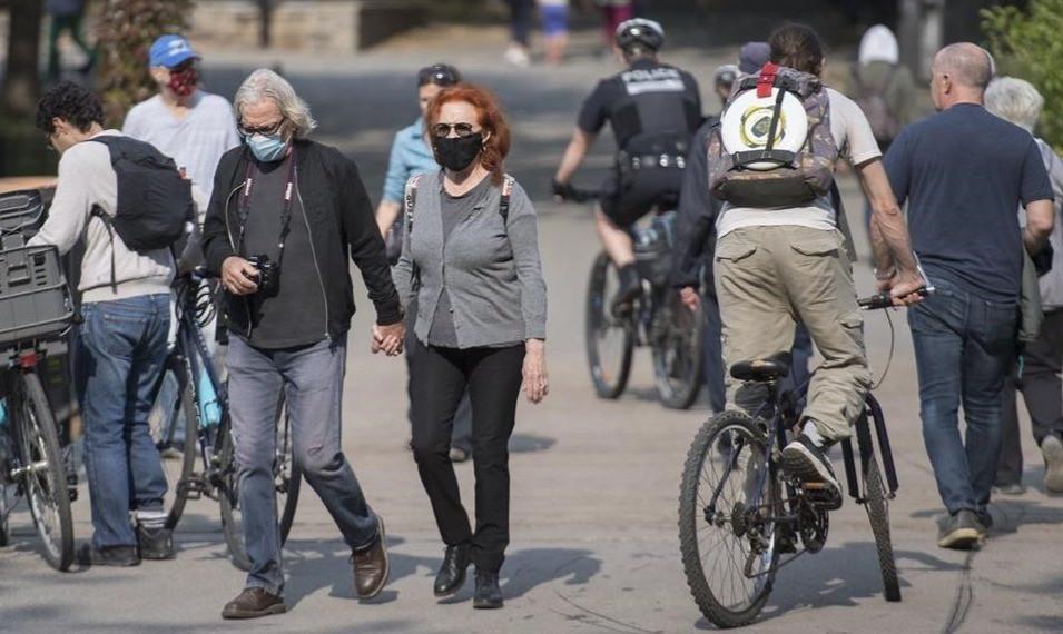 Las personas usan máscaras faciales mientras caminan por un parque de la ciudad de Montreal el 10 de octubre de 2020.