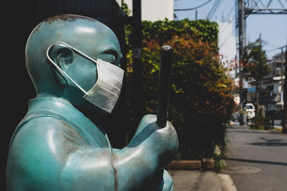 A Japanese statue in Tokyo wearing a disposable mask during the covid-19 epidemic. Passed on a bike tour in Tokyo.
