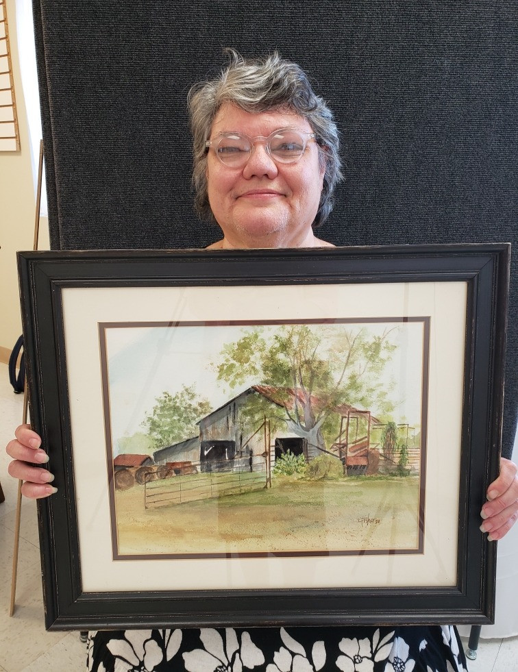 Pictured, Theresa Fisher shows off her painting, Cow Shooter, created during the 2020 Pike Road Plein Air Paint Out.