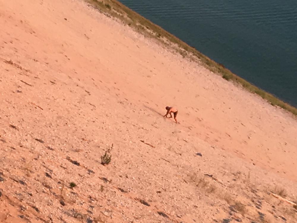 man climbing up a steep sand dune