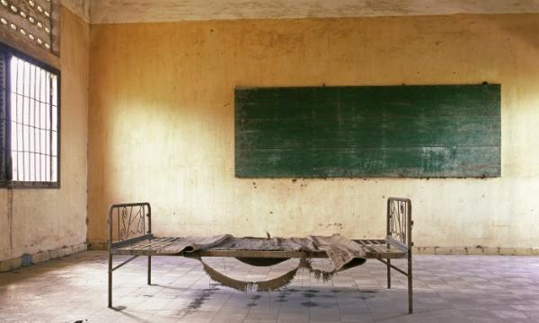 Una cama metálica desvencijada sin colchón en un cuarto grande con pared amarilla en el fondo y un ventanal grande a la izquierda