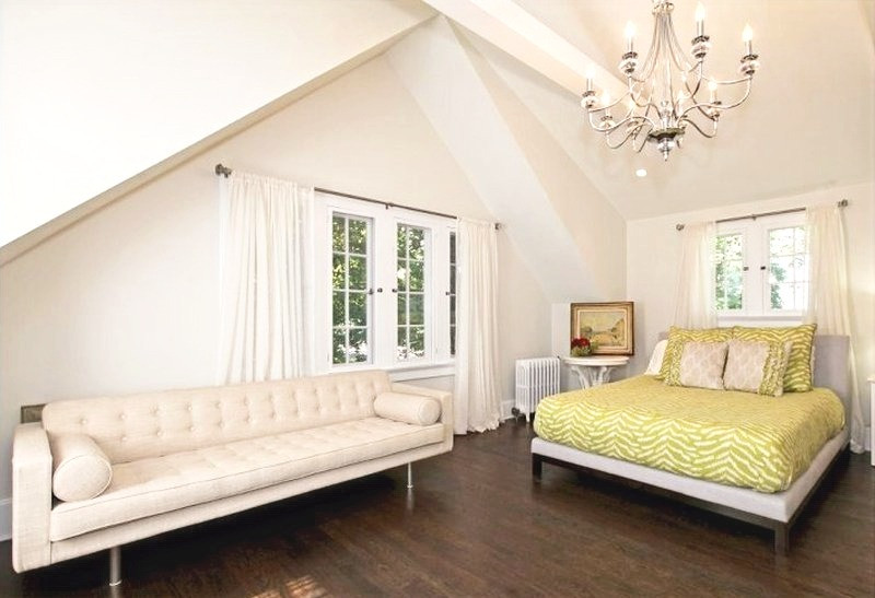Vaulted ceilings, dormers and exposed rafter ties, chandelier and large sofa.